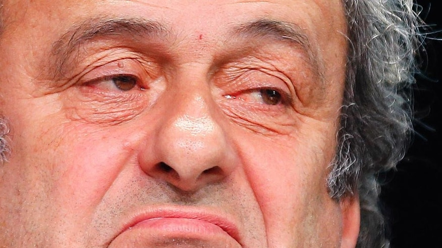 "FILE - In this May 28, 2015 file photo President of UEFA Michel Platini grimaces during a press conference following a meeting of the UEFA board ahead of the FIFA congress in a hotel in Zurich, Switzerland. Complaining that he is being ""dragged through the mud"" in the FIFA corruption investigation, Michel Platini believes he is ""bullet proof"" and has not lost support in his bid to replace Sepp Blatter as the head of world soccer's governing body. The UEFA president, who has been suspended for 90 days along with Blatter, confirmed in an interview published Monday, Oct. 19, 2015 in the French daily Le Monde that he had no written contract for the $2 million payment he received from FIFA in 2011. (AP Photo/Michael Probst, File)"