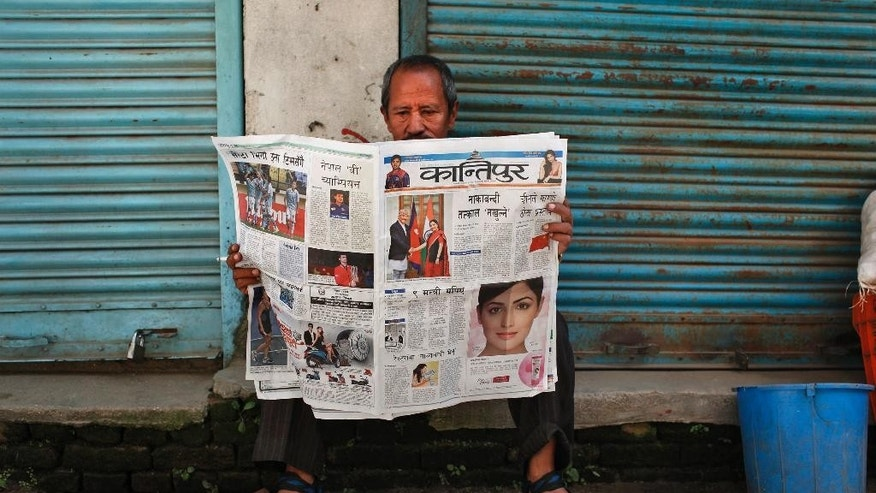 A Nepalese man reads a newspaper in Kathmandu, Nepal, Monday, Oct. 19, 2015. Nepal's Deputy Prime Minister and Foreign Minister Kamal Thapa visited India for talks to resolve the India-Nepal border impasse which has left the Himalayan nation hobbled by a shortage of fuel and goods as the ethnic Madhesis protest against the new constitution of Nepal. (AP Photo/Niranjan Shrestha)