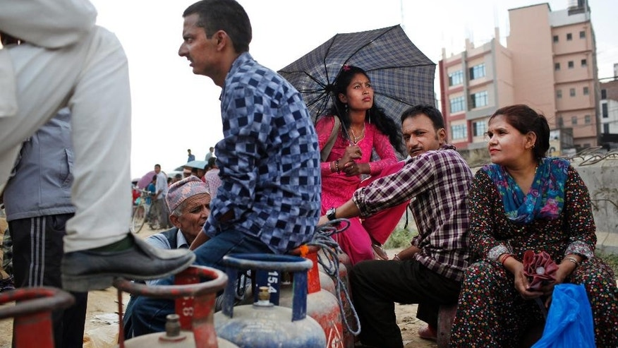 Nepalese people sit near empty cooking gas cylinders as they wait for fresh supply in Kathmandu, Nepal, Monday, Oct. 19, 2015. Ethnic minority groups, mainly the Madhesi in the south and southeast and Tharu in the southwest, have been protesting since Nepalese lawmakers began to finalize the much-delayed constitution, which was approved by the country's Parliament on Sept. 20 despite the protests. The Madhesi groups blocked several border points, and India, which supports the groups, blocked the flow of trucks bringing in fuel and other supplies to Nepal. That created a severe fuel shortage and threatens to disrupt Hindu festivals to be held this month. (AP Photo/Niranjan Shrestha)