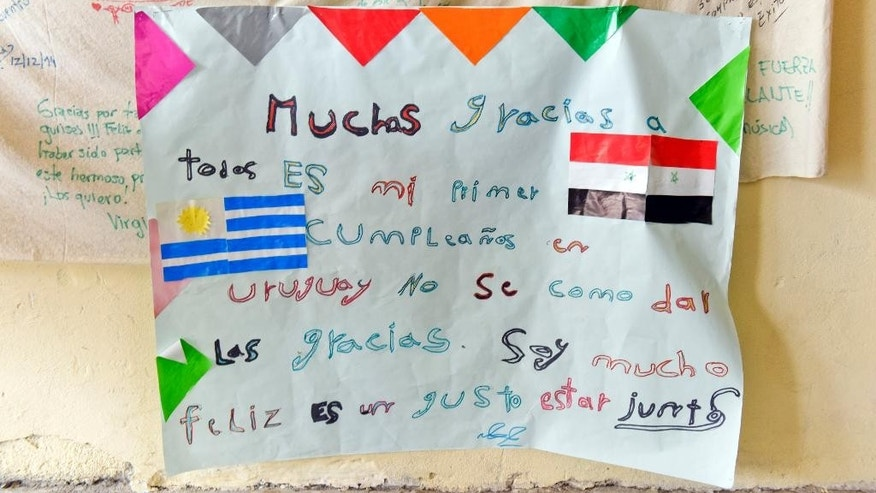 "In this Oct. 7, 2015 photo, a hand written letter by a Syrian refugee from the Alshebli family hangs inside the education center where some family members take classes in Juan Lacaze, Uruguay. It reads in Spanish: ""Thank you everyone. This is my first birthday in Uruguay. I don't know how to thank you. I'm very happy and it's a pleasure to be together."" However, the child's father, Merhi, is frustrated with his host country's high cost of living, and that Uruguay doesn't have the authority to issue him a visa for another country. (AP Photo/Matilde Campodonico)"