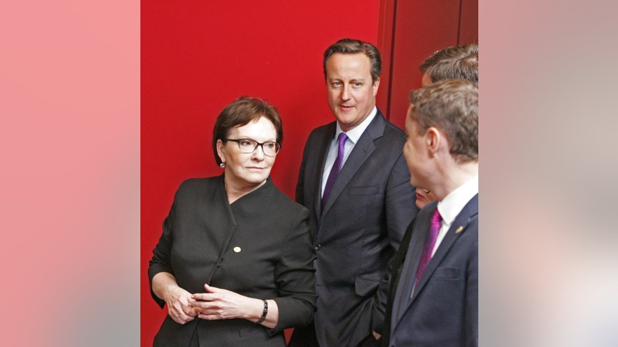 Polish Prime Minister Ewa Kopacz, left, speaks with Estonian Prime Minister Taavi Roivas, right, and British Prime Minister David Cameron, second left, after a group photo at an EU summit in Brussels on Thursday, Oct. 15, 2015. European Union heads of state meet Thursday to discuss, among other issues, the current migration crisis. (AP Photo/Francois Walschaerts)
