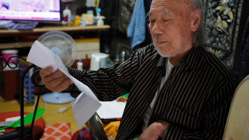 In this Oct. 15, 2015 photo, South Korean Kim Wu-jong, 87, who will travel to North Korea to meet his younger sister, looks at a document from the Red Cross during the interview at his home in Seoul, South Korea. Kim and about 640 other South Koreans will meet their North Korean relatives at the authoritarian country's scenic Diamond Mountain resort in a reunion program that begins Tuesday, Oct. 20. Tens of thousands of people on both sides of the Demilitarized Zone desperately seek such reunions, but the two countries have pulled off relatively few of them. (AP Photo/Lee Jin-man)