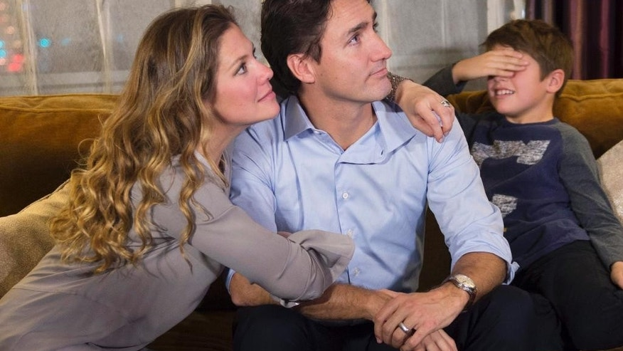 Xavier Trudeau, right, covers his eyes as Liberal leader Justin Trudeau watches the election results with his wife Sophie Gregoire at a hotel in downtown Montreal on Monday, Oct. 19, 2015. (Paul Chiasson/The Canadian Press via AP) MANDATORY CREDIT