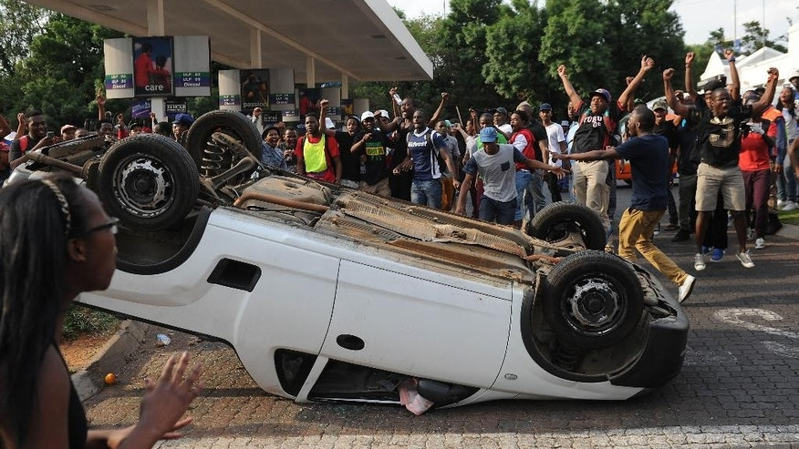 Students from the University of the Witwatersrand overturn a vehicle off campus after blocking traffic, during protests in Johannesburg, Monday Oct. 19 2015. Students, demonstrating against the increase of tuition fees at some top South African universities, blocked roads and entrances and  caused the suspension of classes on some campuses. (AP Photo)