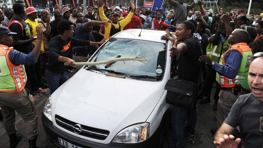 Students from the University of the Witwatersrand smash a vehicle off campus after blocking traffic, during protests in Johannesburg, Monday Oct. 19 2015. Students, demonstrating against the increase of tuition fees at some top South African universities, blocked roads and entrances and  caused the suspension of classes on some campuses. (AP Photo)