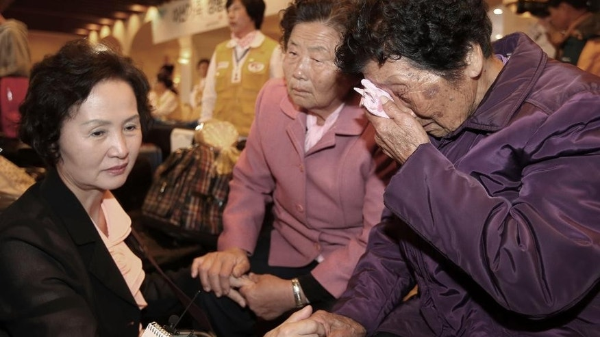 South Korean Sung Soon-hwa, 86, right, weeps as she arrives to take part in family reunions with her North Korean family members at a hotel in Sokcho, South Korea, Monday, Oct. 19, 2015.  About 640 other South Koreans will meet their North Korean relatives at the authoritarian country's scenic Diamond Mountain resort in a reunion program that begins Tuesday.  (AP Photo/Yonhap, Kim Do-hoon) KOREA OUT