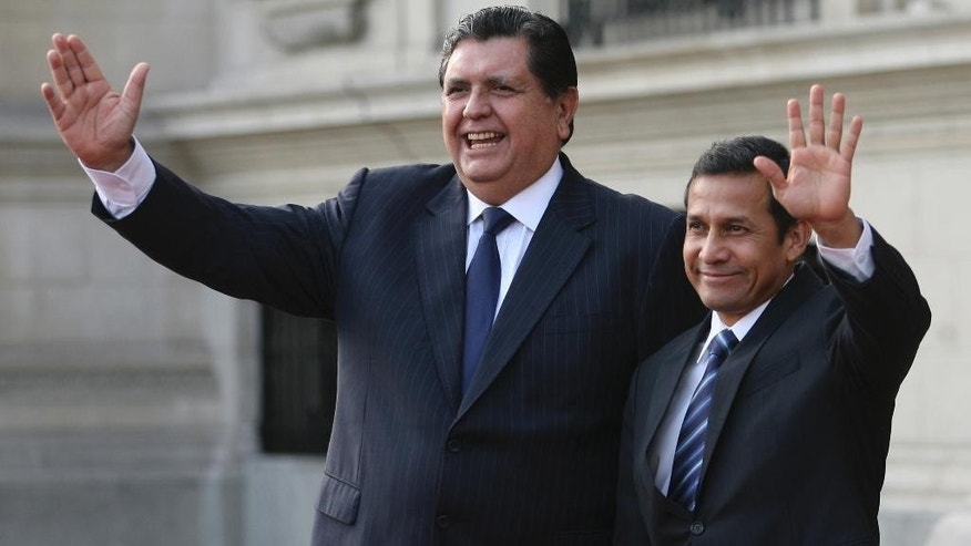 FILE - In this Friday, June 17, 2011 file photo, Peru's outgoing President Alan Garcia, left, and Peru's President-elect Ollanta Humala wave to reporters during a meeting at the government palace in Lima, Peru. Garcia is, as of Monday, Oct. 19, 2015, an official candidate for a third term as Peru's president, with elections due in April. (AP Photo/Marcelo Luna, File)