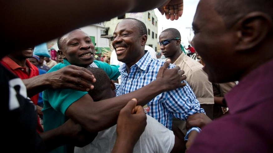 In this Oct. 17, 2015 photo, supporters greet presidential candidate Moise Jean Charles, of the Platform Pitit Dessalines political party, as he campaigns in Port-au-Prince, Haiti. This year's unprecedented three rounds of balloting will pick Haiti's next president, two-thirds of the Senate, the entire Chamber of Deputies and local offices. The Oct. 25 vote is expected to clear the sprawling presidential field for a runoff Dec. 27 between the top two finishers. (AP Photo/Dieu Nalio Chery)