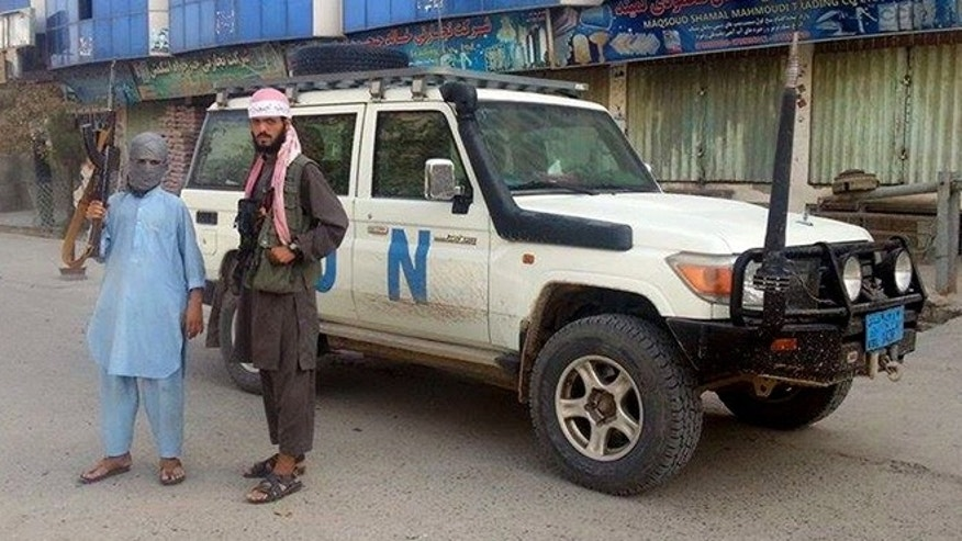 Sept. 29, 2015: Taliban fighters pose for a photo next to a UN vehicle they plundered in Kunduz, Afghanistan.