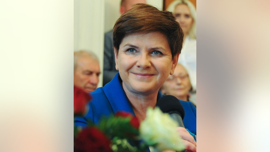 In this Oct. 17, 2015 photo, Law and Justice candidate for the prime minister's post, Beata Szydlo, attends an election campaign meeting in Warsaw, Poland. A quarter century after the fall of communism, Poland is bitterly divided between successful Poles profiting from one of Europe's fastest growing economies and those struggling with low wages and other inequalities of the capitalist era. In an election year dominated by this clash of views, the populist party Law and Justice, with Beata Szydlo as its candidate for prime minister, has tapped into frustration to become the front-runner in parliamentary elections Sunday. (AP Photo/Alik Keplicz)