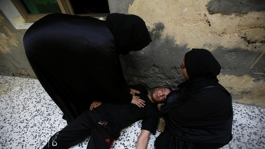 Bahraini women tend to a young man overcome by tear gas during clashes with riot police in the western village of Karzakan, Bahrain, Tuesday, Oct. 20, 2015. Clashes erupted after police began removing street decorations for the Shiite religious occasion of Ashura, a 10-day mourning period for an early Shiite saint. (AP Photo/Hasan Jamali)