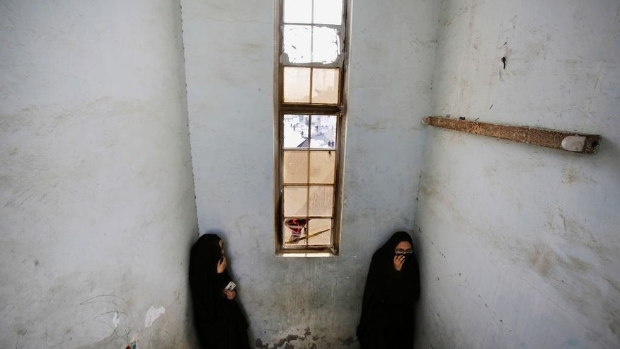 Bahraini women take cover from police tear gas and shotgun fire in a stairwell during clashes in the western village of Karzakan, Bahrain, Tuesday, Oct. 20, 2015. Clashes erupted after police began removing street decorations for the Shiite religious occasion of Ashura, a 10-day mourning period for an early Shiite saint. (AP Photo/Hasan Jamali)