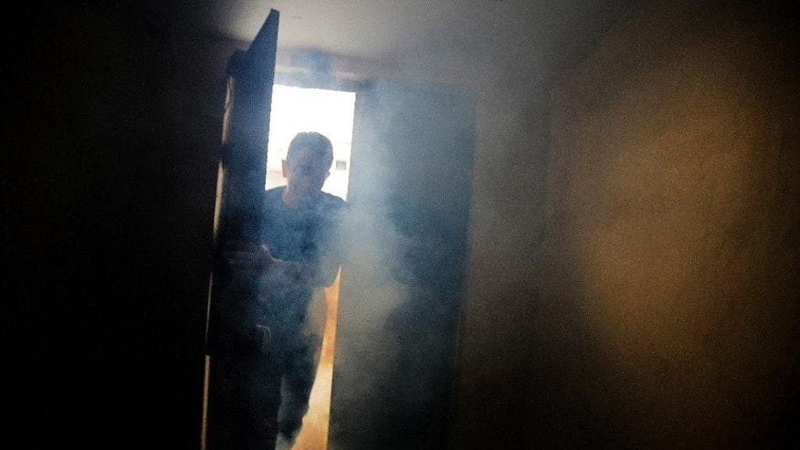 A Bahraini runs into a house in an attempt to escape police tear gas and shotgun fire during clashes in the western village of Karzakan, Bahrain, Tuesday, Oct. 20, 2015. Clashes erupted after police began removing street decorations for the Shiite religious occasion of Ashura, a 10-day mourning period for an early Shiite saint. (AP Photo/Hasan Jamali)