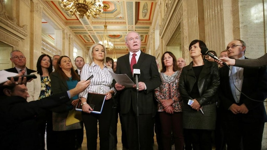 Sinn Fein's Martin McGuinness, centre, stands with members of his party during a press conference at Stormont Parliament in Belfast, Northern Ireland, Tuesday, Oct. 20, 2015 as he gives his reaction in the wake of the publication of a Government-ordered review of paramilitary structures in Northern Ireland. An expert report into the current state of the Irish Republican Army and other outlawed Northern Ireland groups has found that the IRA still exists and some members still pursue violence and crime, but as an organization the group poses no threat to peacemaking. (Niall Carson/PA via AP) UNITED KINGDOM OUT