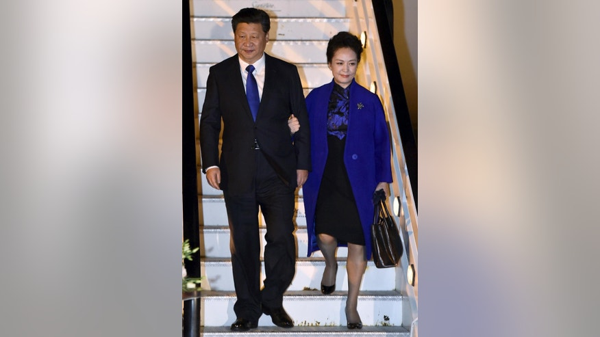 "Chinese President Xi Jinping and his wife Peng Liyuan leave their plane as they arrive at Heathrow Airport, London, Monday, Oct. 19, 2015. Chinese President Xi Jinping arrived in Britain Monday for a four-day state visit as part of a push to increase trade ties between the two countries. Prime Minister David Cameron told Chinese Central Television the visit heralds a ""golden era"" between the two countries. (Toby Melville/Pool photo via AP)"