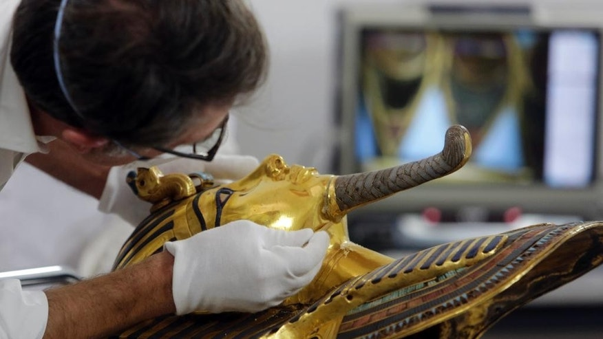 German restorer Christian Eckmann begins restoration work on the golden mask of King Tutankhamun over a year after the beard was accidentally broken off and hastily glued back with epoxy, at the Egyptian Museum in Cairo, Egypt, Tuesday, Oct. 20, 2015. The 3,300-year-old burial pharaonic mask was discovered in Tutankhamun's tomb along with other artifacts by British archeologists in 1922, sparking worldwide interest in archaeology and ancient Egypt. (AP Photo/Amr Nabil)