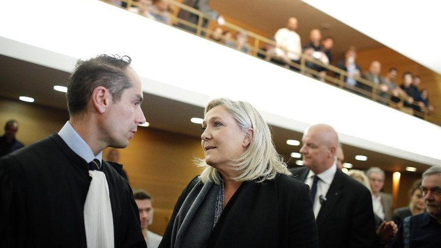 French far-right leader and National Front party president Marine Le Pen, center, speaks with her lawyer David Dassa-Le Deist, left, as she arrives at the Lyon's courthouse, central France, Tuesday, Oct. 20, 2015. Le Pen, whose National Front party is known for its anti-immigration and anti-Islam views, arrived Tuesday in court to be judge on charges of inciting racial hatred in Lyon, where she'll face four anti-racism and human rights organizations. (AP Photo/Laurent Cipriani)