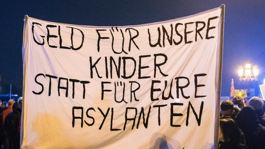 "Protestors hold a banner during a demonstration of the PEGIDA (Patriotic Europeans against the Islamization of the West), marking the first anniversary of the anti-Islam group in Dresden, eastern Germany, Monday, Oct. 19, 2015. The banner reads in German 'Money for our children and not for your asylum seekers'. A surge of migrants to Germany over the summer has fueled a revival of fortunes for the group — whose name stands for ""Patriotic Europeans against the Islamization of the West"" — with crowds to weekly rallies growing steadily. Germany's top security official said the domestic intelligence service was monitoring PEGIDA and called its leaders ""hard far-right extremists."" (AP Photo/Jens Meyer)"