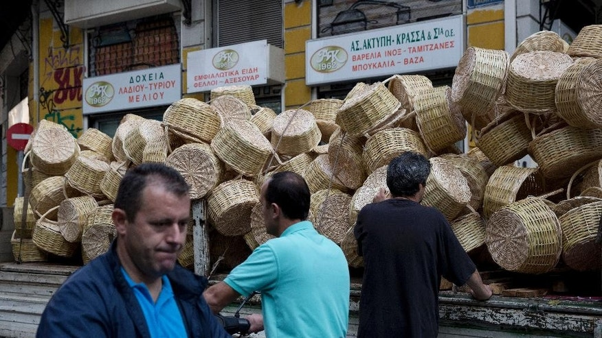 A man loads on a truck wicker baskets in central Athens,on Tuesday, Oct. 20, 2015. Greece's leftwing government has abandoned its pledge to end economic austerity after giving into pressure from bailout lenders to make deeper cuts. But it has promised to embark on major reforms it says long-established political parties were unwilling to make.(AP Photo/Petros Giannakouris)