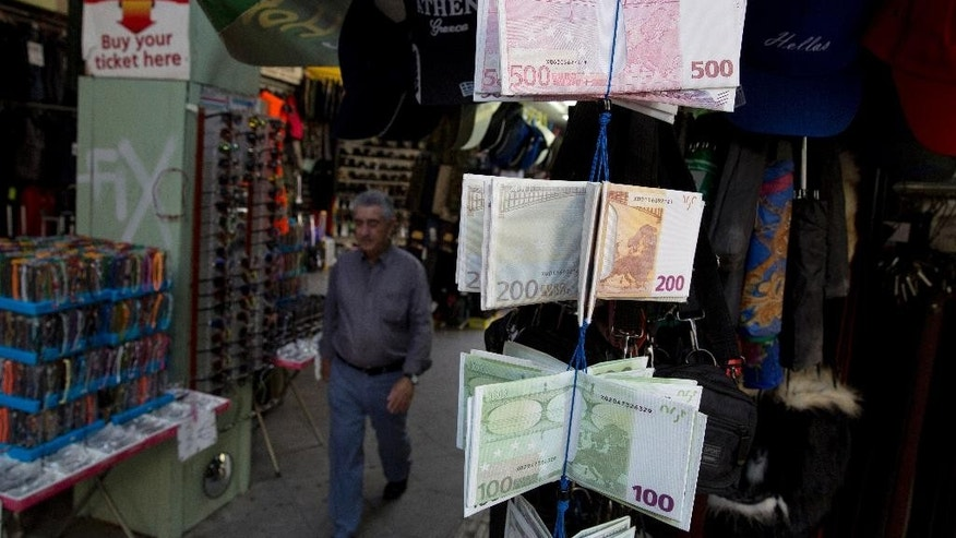 A man  walks past wallets designed as Euro banknotes displayed outside a kiosk in central Athens,on Tuesday, Oct. 20, 2015.Greece's leftwing government has abandoned its pledge to end economic austerity after giving into pressure from bailout lenders to make deeper cuts. But it has promised to embark on major reforms it says long-established political parties were unwilling to make.(AP Photo/Petros Giannakouris)