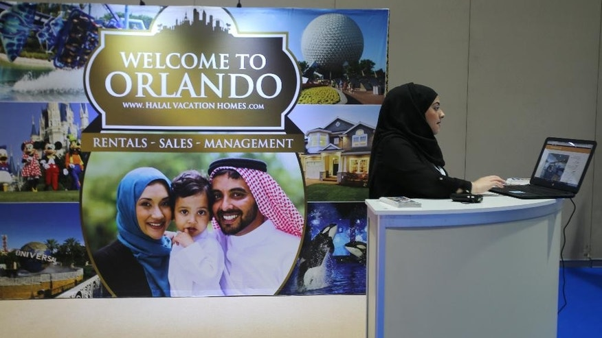In this Oct. 19, 2015 photo, an exhibitor works at an American Halal Vacation Homes booth at The World Halal Travel Summit & Exhibition in Abu Dhabi, United Arab Emirates. Halal tourism is growing as the hospitality industry seeks ways to better serve Muslim travelers, from providing alcohol-free venues to swimming areas that are segregated by gender. (AP Photo/Kamran Jebreili)