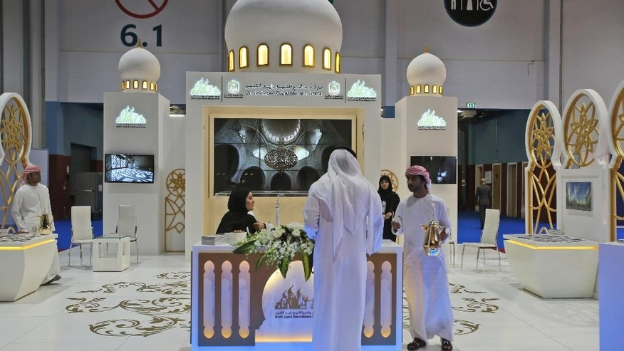 In this Oct. 19, 2015 photo, an exhibitor offers traditional Arabic coffee to a visitor at the Sheikh Zayed Grand Mosque boot during the opening day of The World Halal Travel Summit & Exhibition in Abu Dhabi, United Arab Emirates. Halal tourism is growing as the hospitality industry seeks ways to better serve Muslim travelers, from providing alcohol-free venues to swimming areas that are segregated by gender. (AP Photo/Kamran Jebreili)