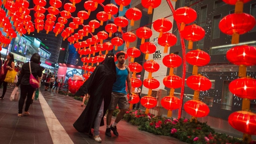 FILE-- In this  Jan. 28,  2015 file photo, a Muslim tourist couple walks under an arch of traditional Chinese lanterns at a shopping mall in Kuala Lumpur, Malaysia. Halal tourism is growing as the hospitality industry seeks ways to better serve Muslim travelers, from providing alcohol-free venues to swimming areas that are segregated by gender. (AP Photo/Joshua Paul, file)