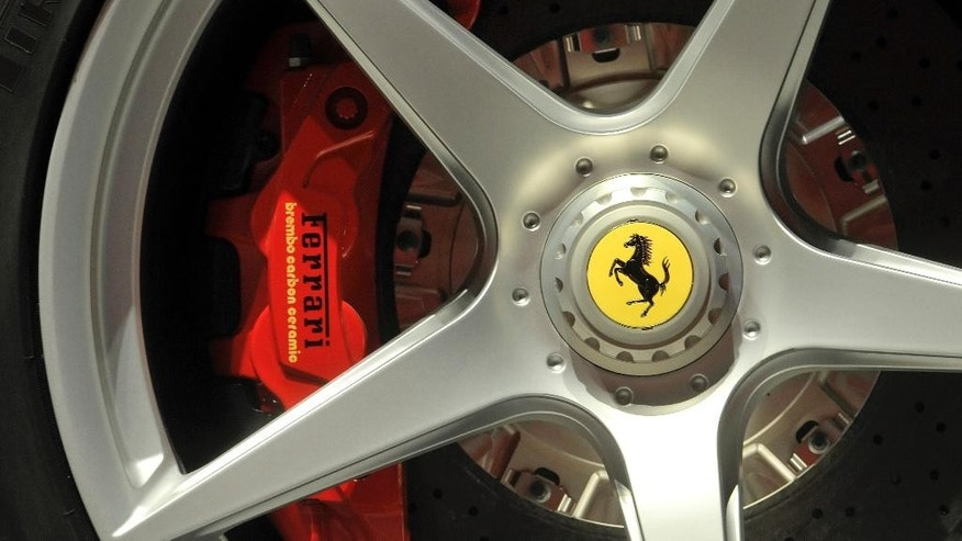 In this May 8, 2013 photo a Ferrari logo is displayed on a wheel at the Ferrari factory in Maranello, Italy. Ferrari is racing toward a public offering on Wall Street on Wednesday Oct. 21, 2015 making it possible for investors to get a piece of the legendary maker of luxury sports cars and powerful Formula 1 racing machines public. (AP Photo/Marco Vasini)