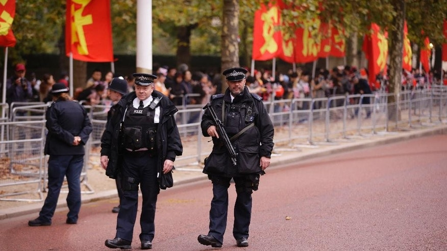 An armed British police officer patrols the Mall before Chinese President Xi Jinping and his wife Peng Liyuan pass by in a carriage ride to Buckingham Palace in London, Tuesday, Oct. 20, 2015. Chinese President Xi Jinping arrived in Britain Monday for a four-day state visit as part of a push to increase trade ties between the two countries. (AP Photo/Matt Dunham)