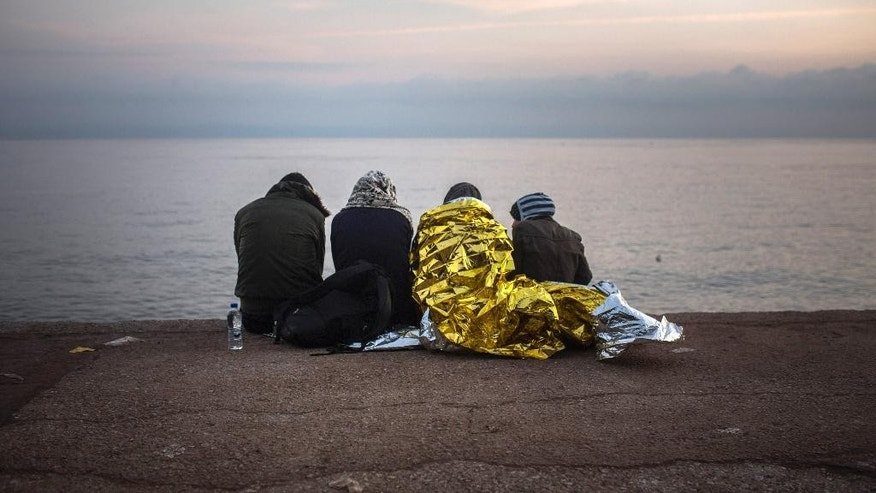 Refugees rest after their arrival from the Turkish coast to Skala Sikaminias village on the northeastern Greek island of Lesbos, early Tuesday, Oct. 20, 2015. Refugee crisis continues unabated as more than 600,000 people, mostly Syrians, have reached Europe since the beginning of this year. (AP Photo/Santi Palacios)
