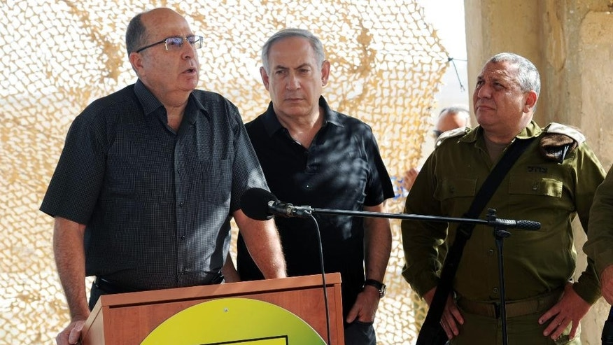 Israeli Defence Minister Moshe Yaalon, left, speaks next to Israel's Prime Minister Benjamin Netanyahu, center,  and Army Chief of Staff Lieutenant-General Gadi Eisenkot, during a visit at a military outpost at the outskirts of Gaza Strip, Tuesday, Oct. 20, 2015. U.N. Secretary-General Ban Ki-moon called for calm during a surprise visit to Jerusalem on Tuesday ahead of meetings with Israeli and Palestinian leaders, in a high-profile gambit to bring an end to a monthlong wave of violence. (Haim Horenstein/Pool Photo via AP)