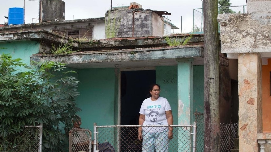 In this Oct. 16, 2015 photo, Maria Victoria Machado stands on her front porch, wearing a T-shirt featuring a stencil art image of her son Danilo Maldonado, better known as El Sexto, in Havana, Cuba. Machado said Tuesday, Oct. 20, 2015, that her son has been freed after 10 months behind bars for attempting to release two pigs painted with the names of Raul and Fidel Castro, the country's current president and former leader. (AP Photo/Desmond Boylan)