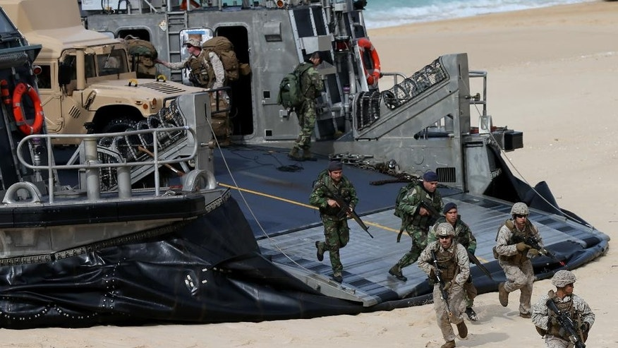 US marines and portuguese fuzileiros get off a US Navy hovercraft after landing at the beach during the NATO Trident Juncture exercise 2015 at Raposa Media beach in Pinheiro da Cruz, south of Lisbon, Tuesday, Oct. 20, 2015. NATO Allies and partner nations join forces for the next three weeks for the Alliance's Trident Juncture live military exercise involving 36,000 troops from more than 30 nations across Portugal, Italy and Spain. (AP Photo/Steven Governo)