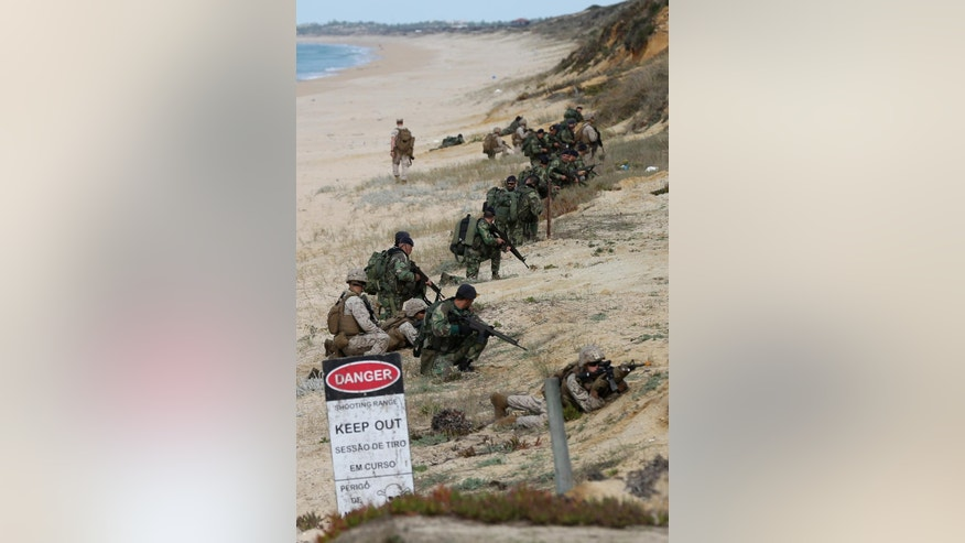 US marines and portuguese fuzileiros hold their positions after getting off US Navy hovercrafts during the NATO Trident Juncture exercise 2015 at Raposa Media beach in Pinheiro da Cruz, south of Lisbon, Tuesday, Oct. 20, 2015. NATO Allies and partner nations join forces for the next three weeks for the Alliance's Trident Juncture live military exercise involving 36,000 troops from more than 30 nations across Portugal, Italy and Spain. (AP Photo/Steven Governo)