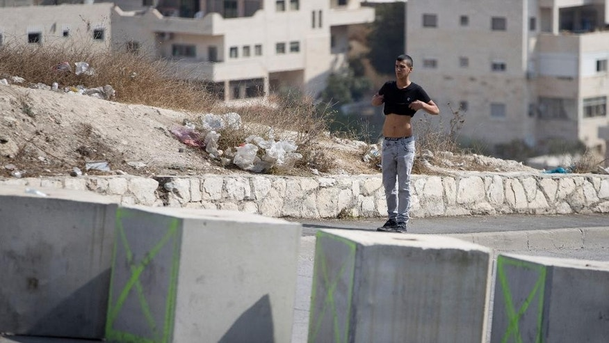 Israeli border police men, not seen, order a Palestinian man to lift his shirt as they check him at a checkpoint before is allowed to exit the Arab neighborhood of Issawiyeh in Jerusalem, Tuesday, Oct. 20, 2015. U.N. Secretary-General Ban Ki-moon will make a surprise visit to Israel and the Palestinian territories on Tuesday, in a high-profile gambit to bring an end to the monthlong wave of violence that has plagued the region. (AP Photo/Ariel Schalit)