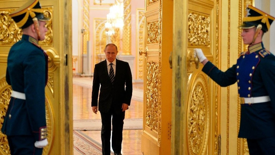 Russia's President Vladimir Putin, center, enters a hall to attend a meeting with senior officers of the Defense Ministry and other government agencies in the Kremlin in Moscow, Russia, Tuesday, Oct. 20, 2015. Putin says intelligence agents have foiled 20 terrorist plots in Russia this year. (Alexei Druzhinin, RIA-Novosti,  Kremlin Pool Photo via AP)