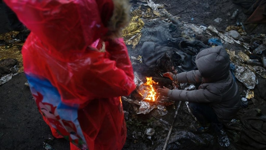 A migrant children gather around a fire to warm themselves, waiting to cross a border line between Serbia and Croatia, near the village of Berkasovo, Serbia, Tuesday, Oct. 20, 2015. Thousands of people trying to reach the heart of Europe surged across Serbia's border into Croatia on Monday after authorities eased restrictions that had left them stranded for days in ankle-deep mud and rain. (AP Photo/Darko Vojinovic)