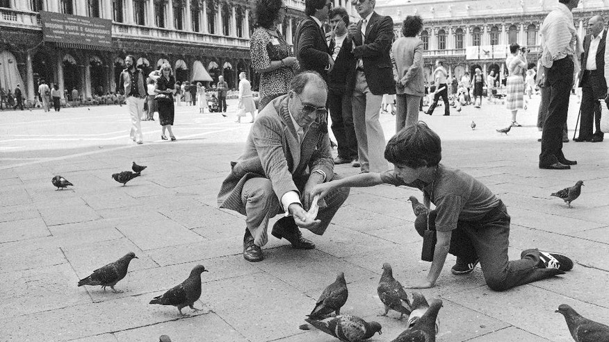 FILE - In this  June 21, 1980, file photo, Canadian Prime Minister Pierre Trudeau kneels at St. Mark's Square in Venice, Italy, with his 8-year-old son Justin as they feed pigeons at the famous square. On Monday, Oct. 19, 2015, Canadian voters reclaimed their country's liberal identity sending Justin Trudeau to the prime minister's office and ending 10 years of conservative leadership under Stephen Harper. At 43, he becomes the second youngest prime minister in Canadian history. (AP Photo/Massimo Sambucetti, File)