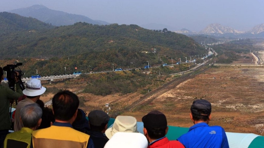 South Korean tourists watch buses carrying South Koreans cross the borderline to Diamond Mountain resort in North Korea, at the Unification Observation post in Goseong, South Korea, Tuesday, Oct. 20, 2015. About 640 South Koreans will be reunited with their North Korean relatives at the Diamond Mountain resort in North Korea from Oct. 20 to 26. (Lee Jong-gun/Yonhap via AP) KOREA OUT