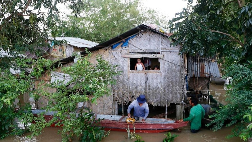 A resident repairs his boat outside of his flooded home from Typhoon Koppu, in La Paz township, Tarlac province, in northern Philippines Tuesday, Oct. 20, 2015. Slow-moving Typhoon Koppu blew ashore with fierce winds in the northeastern Philippines early Sunday, toppling trees and knocking out power and communications and forcing the evacuation of thousands of villagers. (AP Photo/Bullit Marquez)