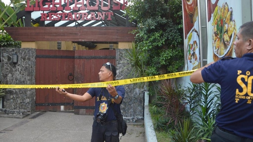 Police mark the crime scene with a yellow tape where two Chinese diplomats were killed in Cebu province, central Philippines on Wednesday Oct. 21, 2015. Two Chinese diplomats in the Philippines were killed and the consul-general was wounded Wednesday by a Chinese attacker armed with a pistol during a birthday celebration at a restaurant, police said. (Alan Tangcawan via AP)