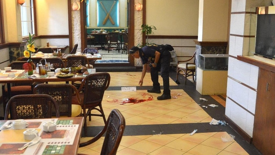An investigator marks the crime scene where two Chinese diplomats were killed inside a restaurant in Cebu province, central Philippines on Wednesday, Oct. 21, 2015. Two Chinese diplomats in the Philippines were killed and the consul-general was wounded Wednesday by a Chinese attacker armed with a pistol during a birthday celebration at a restaurant, police said. (Alan Tangcawan via AP)