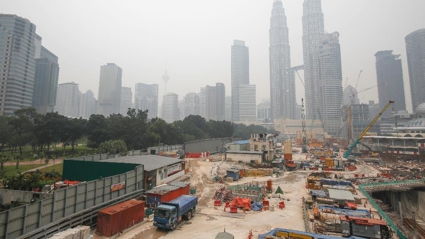Despite the thick haze, construction resumes in front of Malaysia's landmark buildings, Kuala Lumpur Tower, centre left, and Petronas Twin Towers, center right, in Kuala Lumpur, Malaysia, Wednesday, Oct. 21, 2015. Malaysian schools remain closed for a third day due to the haze situation. (AP Photo/Joshua Paul)