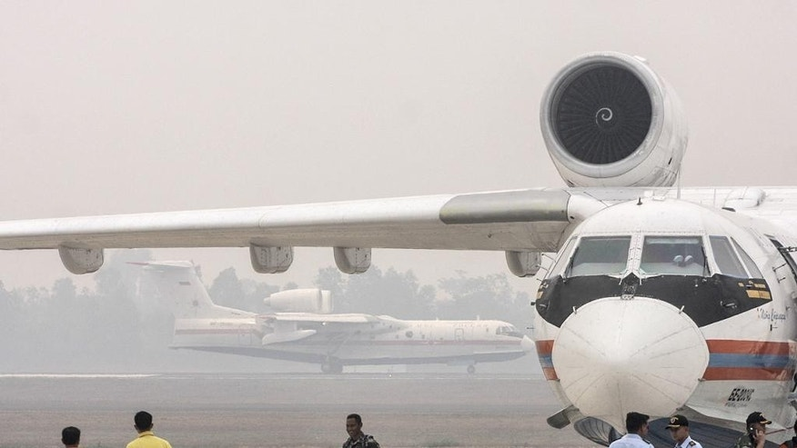 Russian Beriev Be-200 amphibious firefighting jets are parked on the tarmac at the haze-blanketed Sultan Mahmud Baddarudin II Airport in Palembang, South Sumatra, Indonesia, Wednesday, Oct. 21, 2015. Two Be-200 aircrafts leased by the Indonesian government have arrived on Sumatra island to help douse the massive forest and land fires that have caused widespread haze in parts of Southeast Asia. (AP Photo/Bagus Kurniawan)