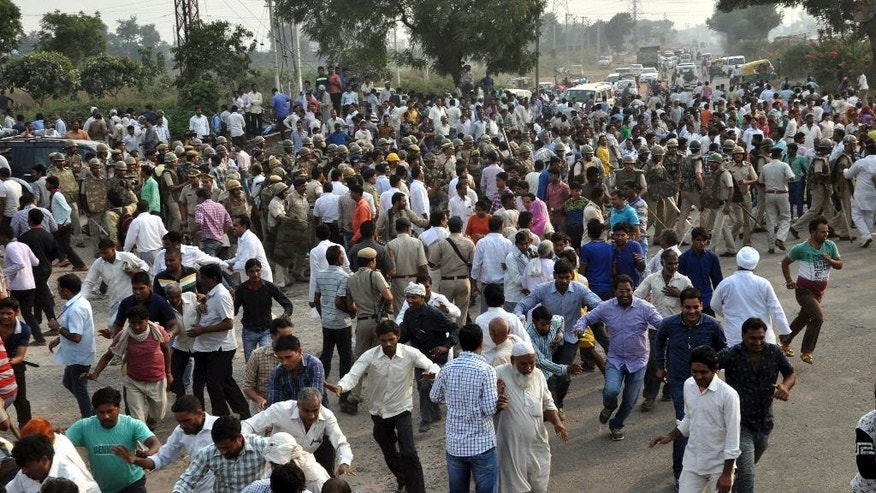 Police try to disperse the crowd after angry residents blocked a highway in Faridabad near New Delhi, India, Wednesday, Oct.21, 2015. The residents blocked the key highway near the Indian capital to demand the attackers be arrested after a baby and a toddler were killed in a house fire allegedly set by their family's upper caste neighbors.(AP Photo/ Vijay Kumar)
