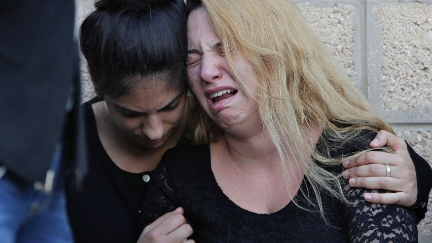 Relatives of the Safwan family mourn near the ambulances carrying the coffins, upon their arrival at Rafik Hariri International Airport in Beirut, Lebanon, Wednesday, Oct. 21, 2015. A rubber boat carrying a family of 12 of their relatives to European shores sunk, drowning seven while tow are still missing. The Lebanese family tragedy highlights how the flood of refugees is encouraging more disenchanted around the region to take the journey to Europe, expected to get riskier in winter. (AP Photo/Bilal Hussein)