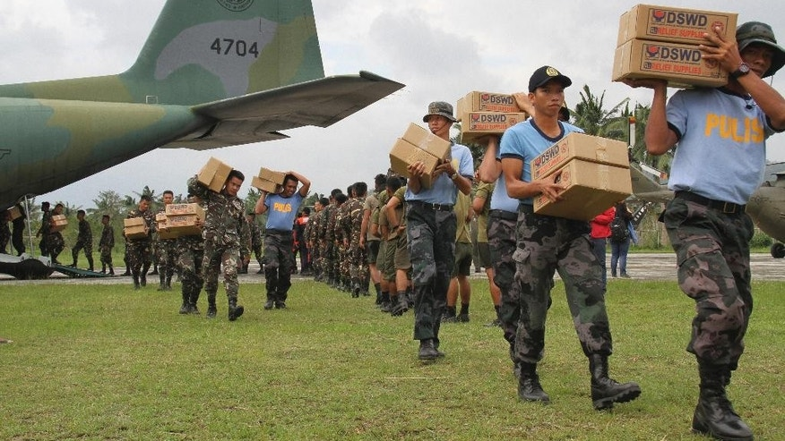 In this photo provided by the Philippine Air Force, Filipino troopers carry relief goods out of a military plane as it lands at the airport in Baler province, northern Philippines Wednesday, Oct. 21, 2015. Tropical Storm Koppu, which barreled ashore as a powerful typhoon in the northeastern Philippines on Sunday before weakening, left several dead and forced more than 100,000 villagers into emergency shelters and destroyed rice fields ready for harvest. (Airman 1st Class Junell Yupangco, PIO/The Philippine Air Force via AP)
