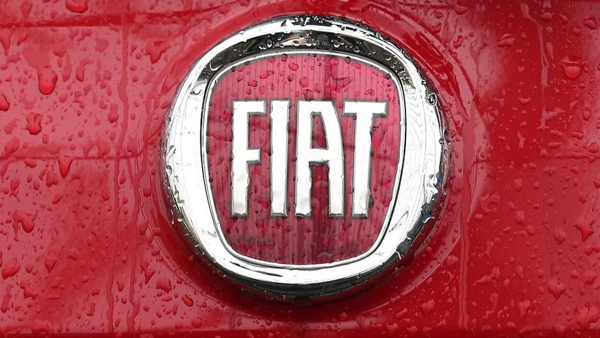 FILE - In this Thursday, Jan. 2, 2014 file photo, rain falls on a Fiat logo pictured on a car  in Milan, Italy. The European Union on Wednesday, Oct. 21, 2015, is demanding that U.S. coffee chain Starbucks and carmaker Fiat repay up to 30 million euros ($34 million) each in tax breaks they received from EU nations, in a major ruling to cut down on sweet tax deals global multinationals often shop for. (AP Photo/Antonio Calanni, File)