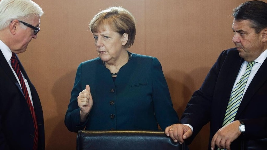 German Chancellor Angela Merkel, center, talks to Foreign Minister Frank-Walter Steinmeier, left, and Vice Chancellor and Economy Minister Sigmar Gabriel prior to the weekly cabinet meeting at the chancellery in Berlin, Germany, Wednesday, Oct. 21, 2015. (AP Photo/Markus Schreiber)