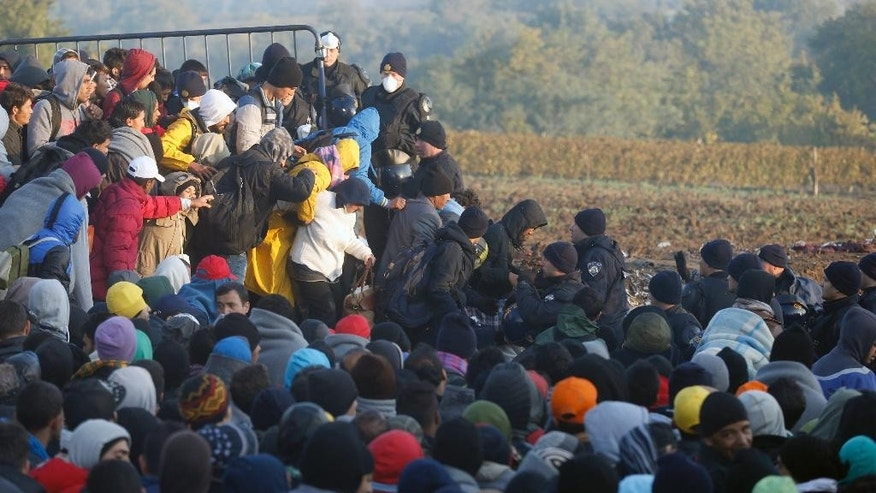 Oct. 21, 2015: Migrants enter into Croatia from Serbia, near the village of Babska, Croatia, as Croatian police officers stand guard by the fence.